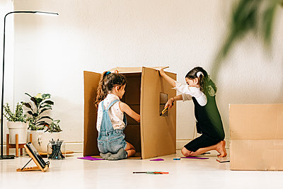 Two little sisters building house with cardboard box - p300m2198106 by Eloisa Ramos