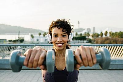 Smiling female athlete with headphones holding dumbbells - p300m2276729 by Xavier Lorenzo