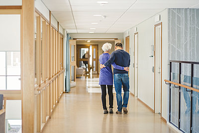 Rear view of senior woman walking with son in corridor at nursing home - p426m2018575 by Maskot