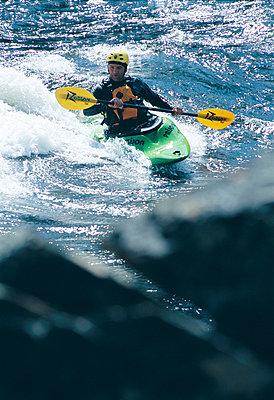 Man canoeing in Trollforsen Sweden - p5751562f by Fredrik Schlyter