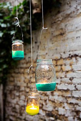 Self-made lanterns hanging at garden wall - p788m1158537 by Lisa Krechting