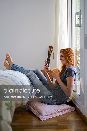 Young woman at home chilling in bedroom and using her smartphone - p300m2118466 by VITTA GALLERY
