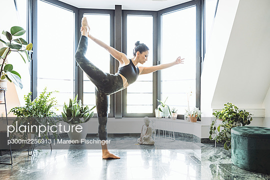 Woman practicing Dancer pose in living room at home - p300m2256913 by Mareen Fischinger