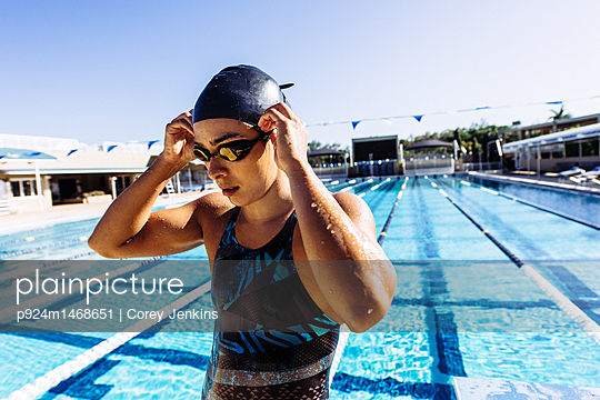 Swimmer in swimming cap and goggles by pool