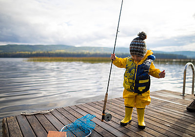 Full length of baby boy wearing raincoat and life jacket while holding fishing rod on wooden pier over lake - p1166m1577774 by Cavan Images