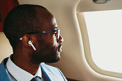 Male entrepreneur with wireless earphones looking through window in private jet - p300m2256387 by OneInchPunch