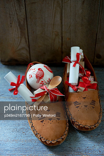 Pair of leather moccasins with red and white gifts - p349m2167798 by Polly Wreford