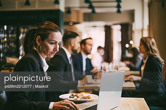 Side view of businesswoman using laptop in restaurant - p426m2212077 by Maskot