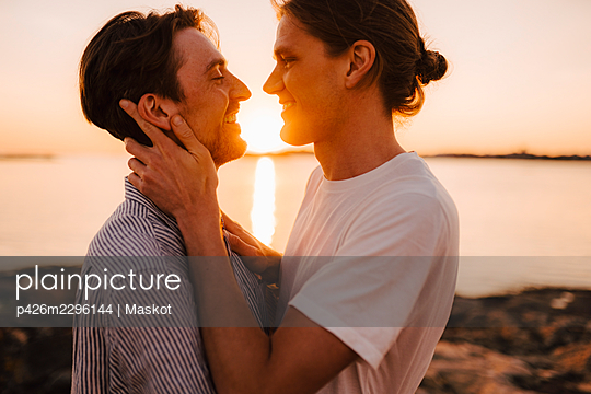 Smiling gay couple standing face to face at lakeshore during sunset - p426m2296144 by Maskot