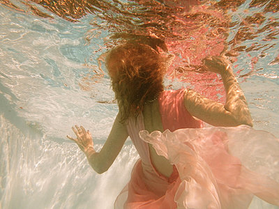 Woman wearing pink dress underwater arching backwards - p1072m829543 by Tracy Jean Shields
