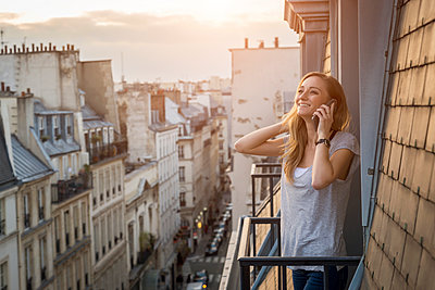 France, Paris, portrait of smiling woman on the phone standing on balcony in the evening - p300m1588091 by JLPfeifer
