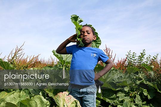 Junge spielt mit einem riesigen Blatt - p1307m1585030 von Agnès Deschamps