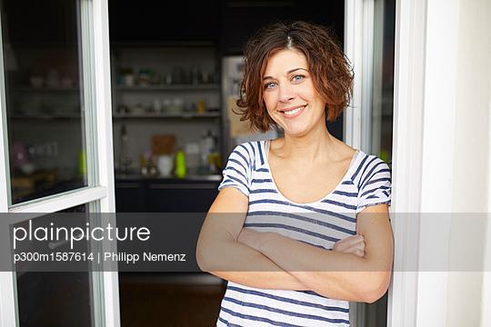Portrait of content mature woman leaning against open balcony door - p300m1587614 von Philipp Nemenz