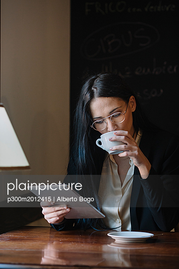 Young businesswoman drinking coffee and using tablet in a cafe - p300m2012415 von Alberto Bogo
