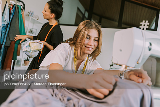 Smiling teenage fashion designer sewing cloths with mature woman in background working at workshop - p300m2286427 by Mareen Fischinger