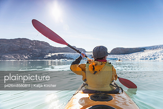 Rear view of mature woman kayaking on sea - p426m858081f by Katja Kircher