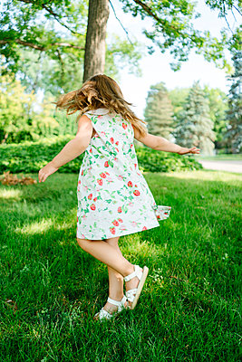 A young girl twirls in a circle outside - p1166m2073672 by Cavan Images