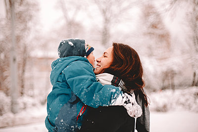 Happy mother holding son while standing in park during winter - p1166m2141037 by Cavan Images