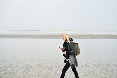 Netherlands, young woman with backpack walking on the beach looking at cell phone - p300m1587736 by Markus Mielek