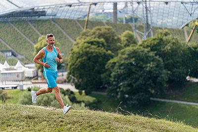 Sporty man jogging in a park - p300m2118938 von Daniel Ingold