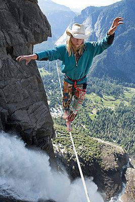 Male highliner walking the Yosemite Falls highline  - p343m1003007f by Jared Alden