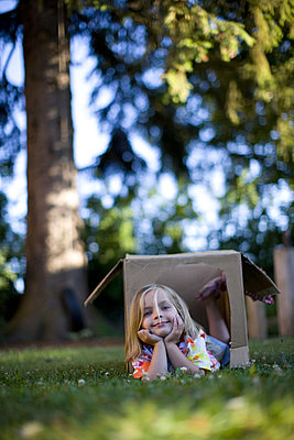 Portrait of little girl laying in a box in the backayrd - p343m1020851 by Woods Wheatcroft photography