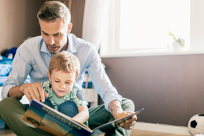 Father pointing and reading book to son while sitting on floor at home - p426m1179354 by Kentaroo Tryman