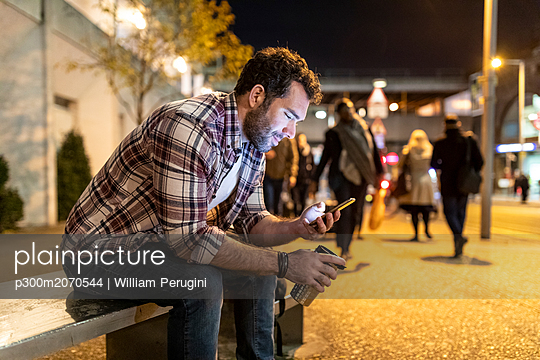 UK, London, smiling man sitting on a bench and looking at his phone by night - p300m2070544 by William Perugini