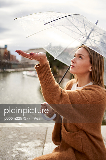 Woman with umbrella sitting on retaining wall during rainy season - p300m2257377 by Veam