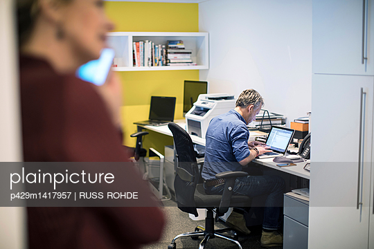 Man sitting at desk in office using laptop computer - p429m1417957 by RUSS ROHDE
