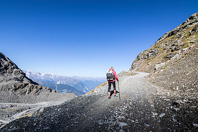 View of senior woman hiking in mountains, Valais, Switzerland - p1166m2202306 by Suzanne Stroeer