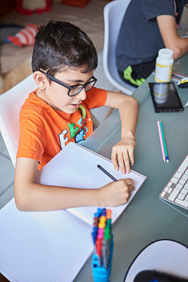 Two boys (8-9, 14-15) learning at desk at home during Covid-19 lockdown - p1427m2235623 by Francisco Navarro
