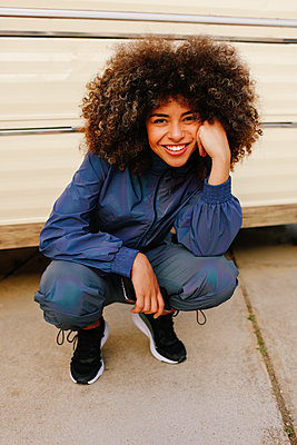 Portrait of happy stylish young woman wearing tracksuit outdoors - p300m2179966 by Lightsy Studio