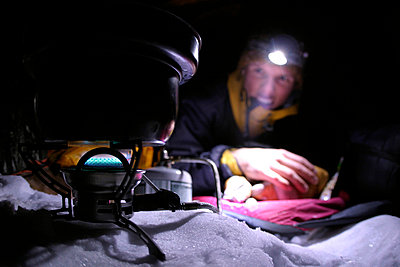 Mountaneer is boiling water and preparing the dinner on his multi fuel kitchen high up in the alps - p3433635 by Patrik Lindqvist