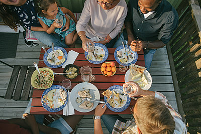 High angle view of multi-generation family having lunch at table on porch - p426m2036523 by Maskot