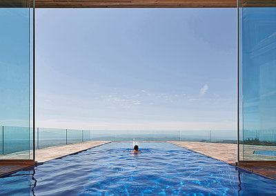 Mixed race man swimming in infinity pool overlooking scenic view - p555m1413638 by Trinette Reed