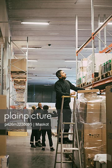 Male entrepreneur standing on ladder while taking inventory at logistics warehouse - p426m2238695 by Maskot
