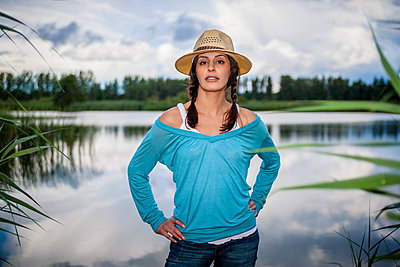 Woman with straw hat with hand on hips on the lakefront  - p1093m2193613 by Sven Hagolani
