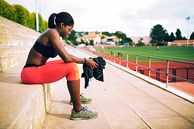 Side view of tired female athlete sitting on steps at stadium - p1166m1086169f by John Trice