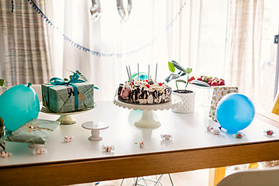 Birthday cake with decorations and gifts arranged on table against window at home - p1166m2067955 by Cavan Images