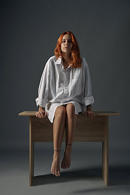 Redhaired woman sitting on a table  - p1561m2134581 by Andrey Cherlat