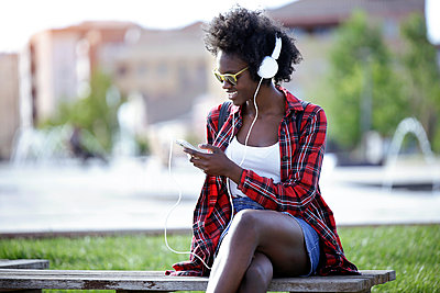 Smiling young woman sitting on bench in city park listening music with headphones - p300m1587563 by Josep Suria