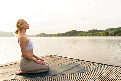 Young woman practicing yoga on a jetty at a lake - p300m2140091 by Joseffson