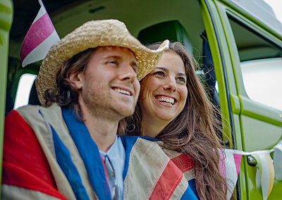 Smiling woman with boyfriend in camper van looking away - p300m2250368 by LOUIS CHRISTIAN