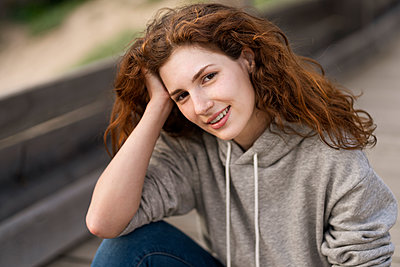Smiling beautiful woman with hand in hair sitting on bridge - p300m2286842 by Steve Brookland