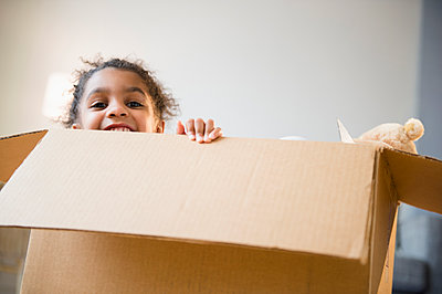 African American girl playing in cardboard box - p555m1415566 by JGI/Jamie Grill