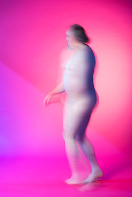 Naked man dancing in front of a pink background - p590m2015837 by Philippe Dureuil