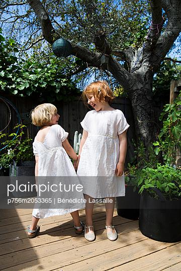 Zwei Schwestern spielen auf der Terrasse - p756m2053365 von Bénédicte Lassalle
