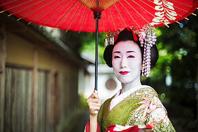 A woman dressed in the traditional geisha style, wearing a kimono and obi, with an elaborate hairstyle and floral hair clips, with white face makeup with bright red lips and dark eyes holding a red paper parasol.  - p1100m1185726 by Mint Images