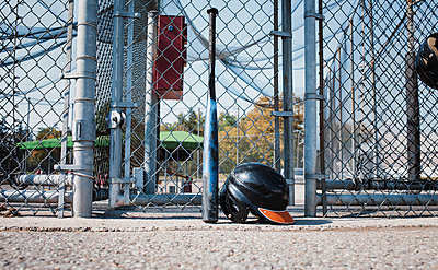 Baseball bat and sports helmet against chainlink fence at playing field during sunny day - p1166m1509794 by Cavan Images